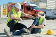 Leinwanddruck Bild - injured lying worker at work being assisted