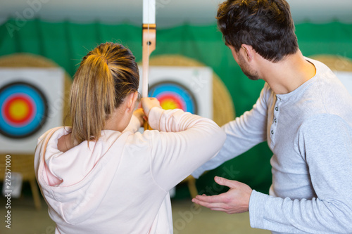 rear view of woman aiming at archery target Fototapete