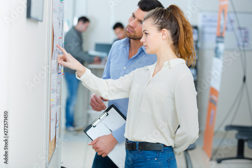 Obraz man and young lady consulting notice board - fototapety do salonu