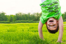 Cheerful Boy Upside Down On The Grass