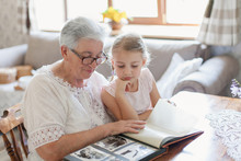 Grandmother And Granddaughter Watching Old Photo Album At Home. Senior Woman Shows Child Black And White Photos. Retired Person And Kid Are Happy. Family Leisure.