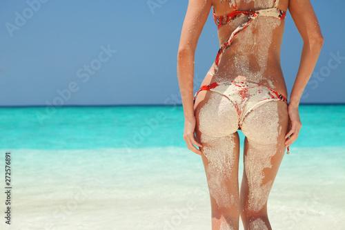 Obraz Sandy woman body in bikini. Summer beach concept. Sexy woman buttocks on blue sea and blue sky background. Beautiful tanned summer woman body - fototapety do salonu