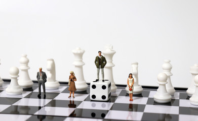 Chess horses and miniature people. A miniature man standing on a dice.