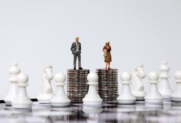 Miniature people standing on a pile of coins on a chessboard.