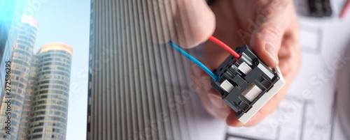 Fotografía Electrician connecting a wire into a power socket; multiple expo