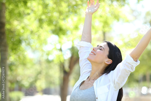 Stampa su Tela  Happy woman celebrating new day raising arms in a park