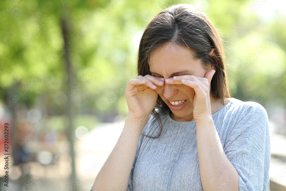 Fototapeta Disgusted woman rubbing her eyes in a park