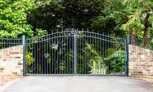Metal Driveway Property Entrance Gates Set In Brick Fence With Garden Trees  In Background