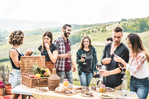 Happy adult friends eating at picnic lunch in italian vineyard outdoor - Young p Wallpaper Mural
