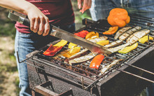 Young Woman Cooking Organic Vegetables At Barbecue Dinner Outdoor - Couple Grilling Peppers And Aubergines For Vegan Bbq - Vegetarian And Healthy Lifestyle Concept - Focus On Left Girl Hand
