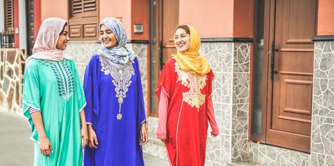 Sretni arapski prijatelji u šetnji centrom grada s tradicionalnom islamskom odjećom - Mlade Arapkinje zajedno se zabavljaju - Koncept prijateljstva, mladih, etničke kulture i religije - Fokus na ljude