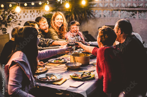 Happy family cheering with red wine at barbecue dinner outdoor - Different age o Fotobehang