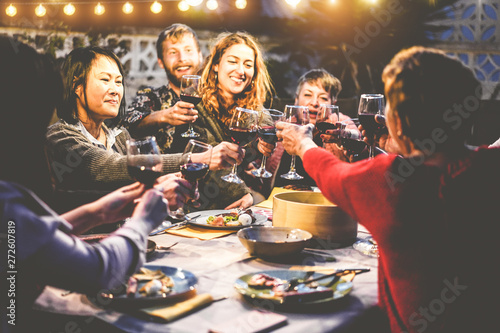 Fototapeta Happy family eating and drinking wine at barbecue dinner outdoor - Multiracial mature and young people having fun at bbq sunday meal - Food and summer lifestyle concept - Focus on asian woman face obraz na płótnie