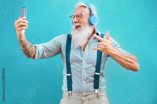Tela Senior hipster man using smartphone app for creating playlist with rock music -