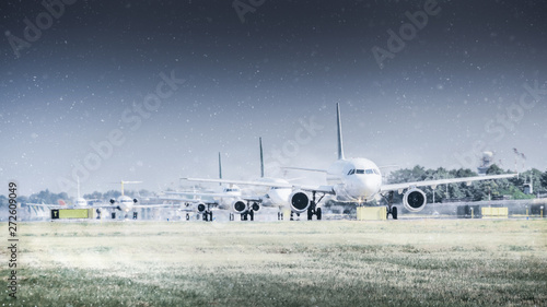 Fényképezés  Row of commercial airplanes on runway delayed due to a winter blizzard