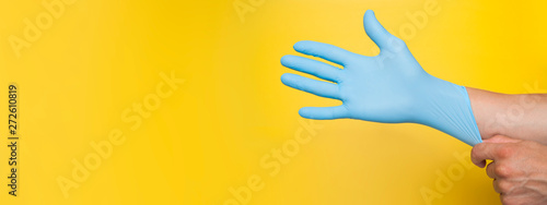 Doctor putting on protective blue gloves isolated on yellow background Canvas Print