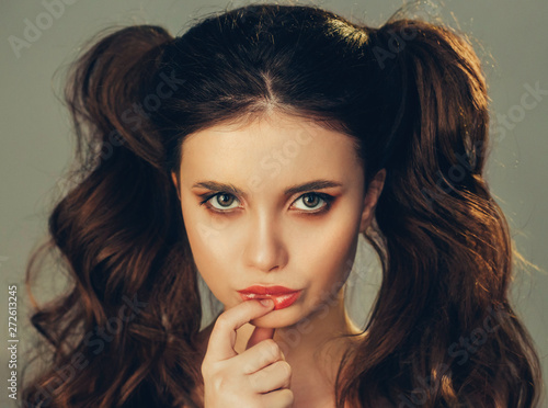 portrait of adult sexy seductive girl with dark hair playing child, girl with two tails thoughtfully raised finger to juicy lips, perfect make-up in style of baby face Canvas-taulu