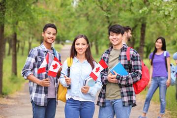 Skupina učenika s kanadskim zastavama na otvorenom