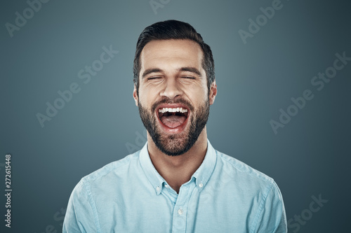Fototapeta So much fun! Handsome young man laughing while standing against grey background obraz