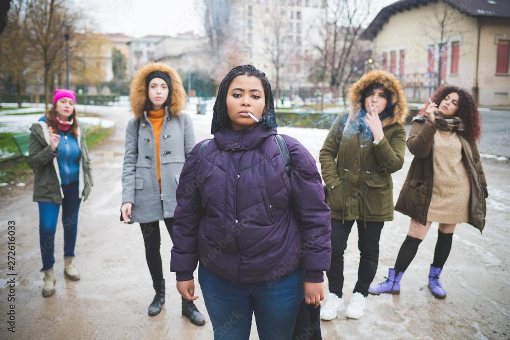 Fototapeta group of young multiracial women smoking cigarette in the street
