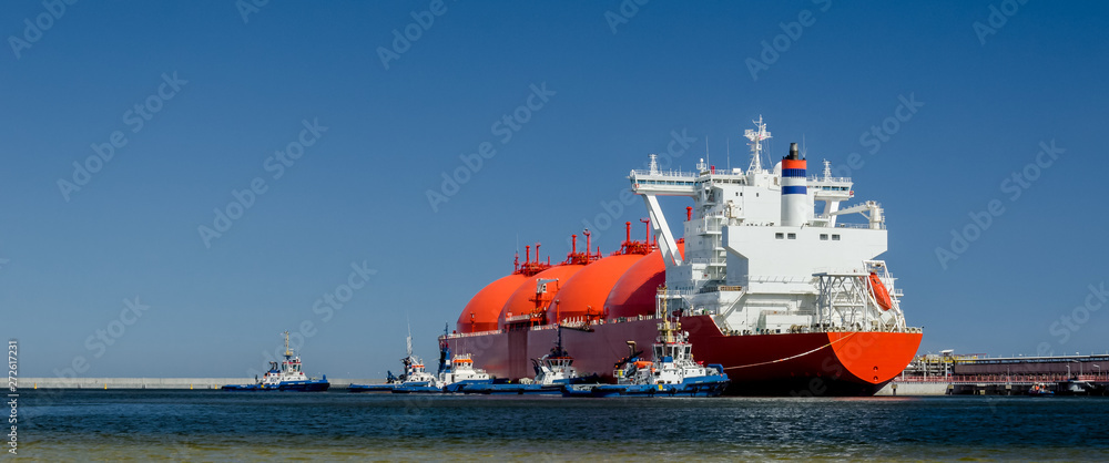 Fototapeta RED LNG TANKER AND SWARM OF TUGBOATS - A giant ship moored to the gas terminal in Swinoujscie