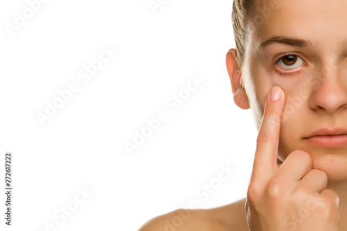 Obraz Young woman pulling her lower eyelid with her finger on white background - fototapety do salonu
