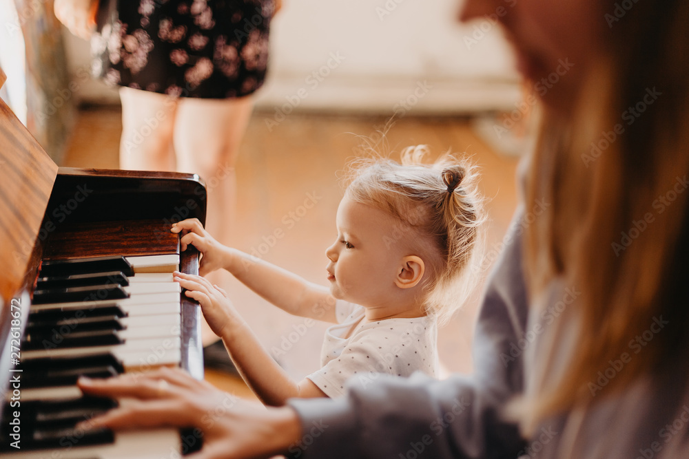 Fototapety, obrazy: Mother teaches a little girl to play the piano. They play and sing songs. Its fun, Cute happy child girl playing piano in a light room. Selective focus, noise effect