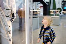 Little Caucasian Boy Looking Astronaut Space Suit In Museum