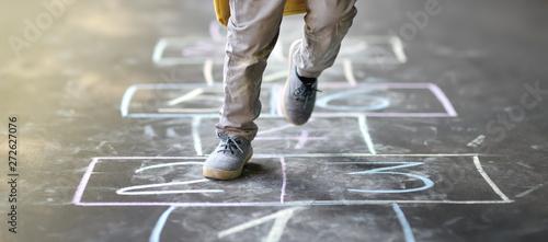 Foto Closeup of little boy's legs and hopscotch drawn on asphalt