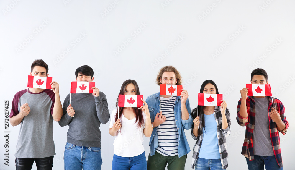 Fototapety, obrazy: Group of students with Canadian flags on light background