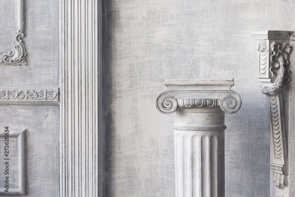 Stone column on light gray background. Close-up, copy space, front view
