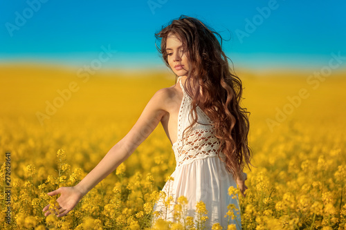 Montage in der Fensternische Honig Beautiful carefree girl with long curly healthy hair over Yellow rape field landscape background. Attracive brunette with blowing hairstyle enjoying sunset, outdoor beauty portrait.
