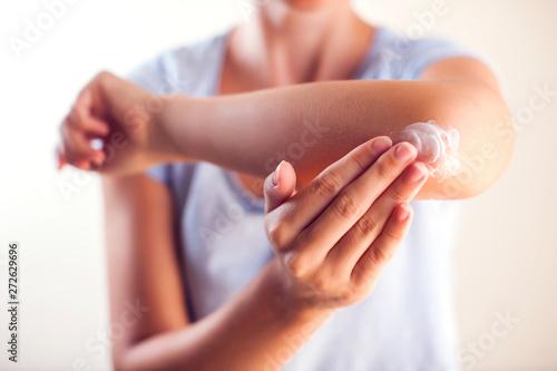 Woman applies cream on dry elbow Fototapeta