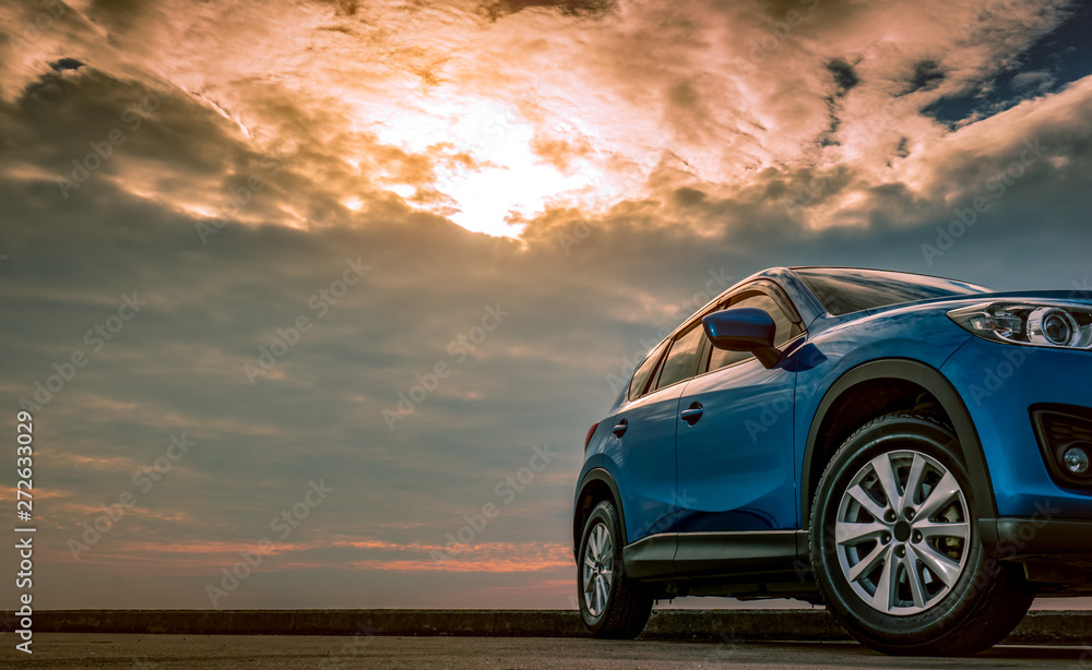 Fototapeta Blue compact SUV car with sport and modern design parked on concrete road by the sea at sunset in the evening. Hybrid and electric car technology concept. Car parking space. Automotive industry.