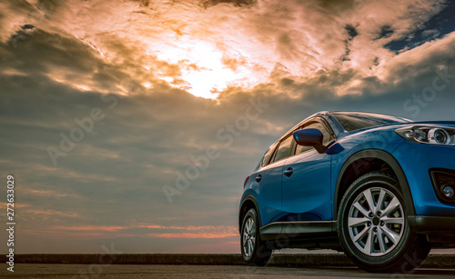 Foto  Blue compact SUV car with sport and modern design parked on concrete road by the sea at sunset in the evening