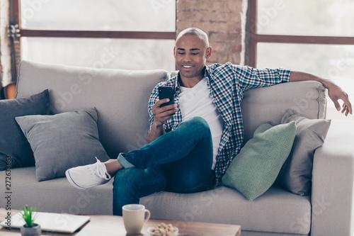 Fotografija Portrait  of positive cheerful trendy stylish guy youth sit divan hold hand devi