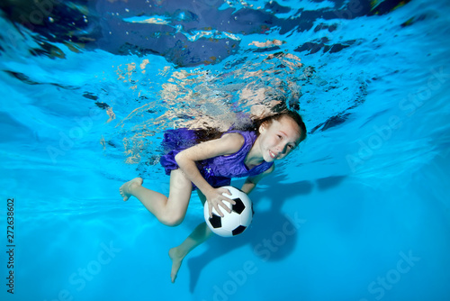 Photo  Happy little girl swimming and playing underwater with soccer ball