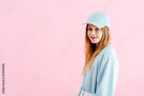 Fotografia  happy pretty teenage girl in cap looking at camera isolated on pink