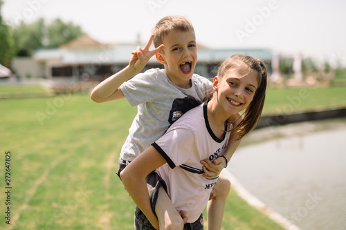 kids playing outdoor. girl holding her brother piggyback Wallpaper Mural