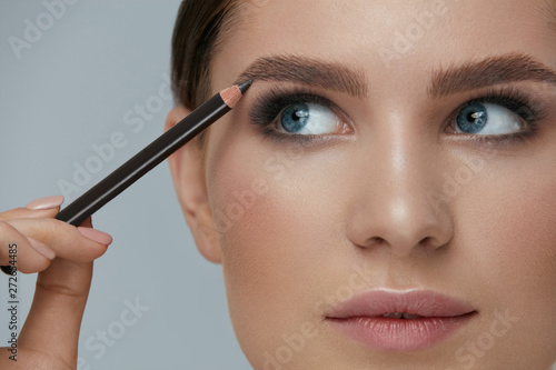 Fotografía Beauty makeup. Woman shaping eyebrow with brow pencil closeup