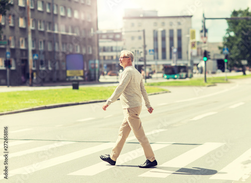 leisure and people concept - senior man walking along summer city crosswalk Fototapete