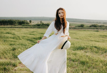 Beautiful Carefree Long Hair Asian Girl In White Clothes And Straw Hat Enjoys Life In Nature Field At Sunset. Sensitivity To Nature Concept