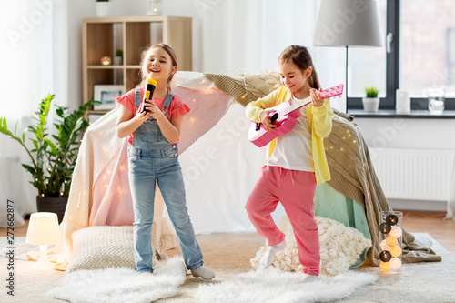 Fototapeta childhood, hygge and friendship concept - happy girls with guitar and microphone
