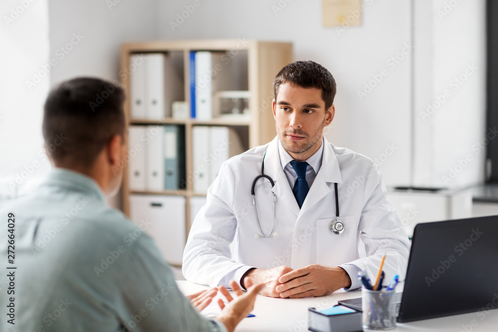 Fototapety, obrazy: medicine, healthcare and people concept - doctor talking to male patient at medical office in hospital