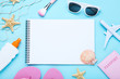 Blank sheet of paper with seashells and beach accessories on blue background
