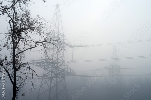Valokuvatapetti High-voltage electric tower in the fog against the background of the forest