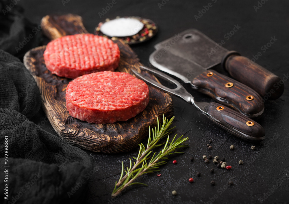 Fototapety, obrazy: Fresh raw minced homemade farmers grill beef burgers on vintage chopping board with spices and herbs and meat hatchet, fork and knife on black board.