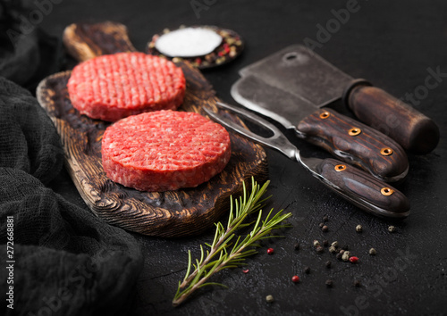 Fresh raw minced homemade farmers grill beef burgers on vintage chopping board with spices and herbs and meat hatchet, fork and knife on black board Fototapet