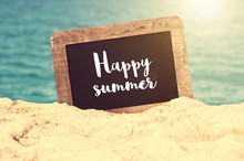 Happy Summer Written On A Vintage Chalkboard In The Sand Of A Beach
