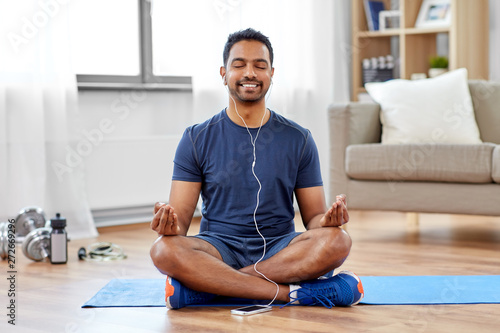 fitness, meditation and healthy lifestyle concept - indian man in earphones listening to music on smartphone and meditating in lotus pose at home - 272669296